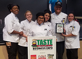 Culinary arts students and Chef Pearson pose with their first place plaque at Taste of Northwest.